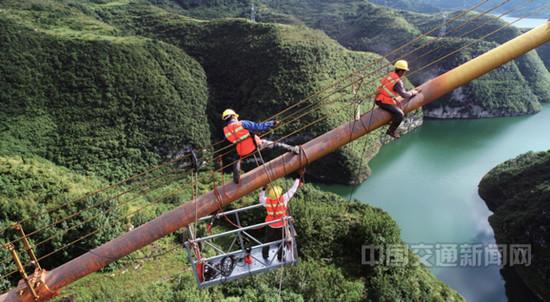 321国道西溪大桥维修养护工作进行中,施工人员对大桥主缆进行除锈作业
